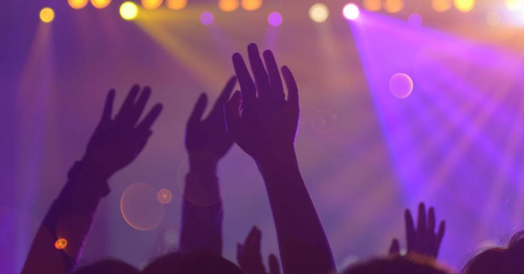 Silhouette of concert-goer hands in air