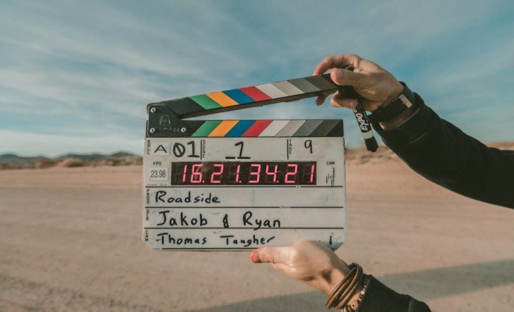 A set of hands hold a clapper board for film making in front of a beach