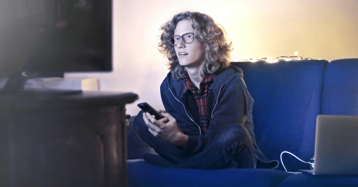 young male watching tv with mobile devices